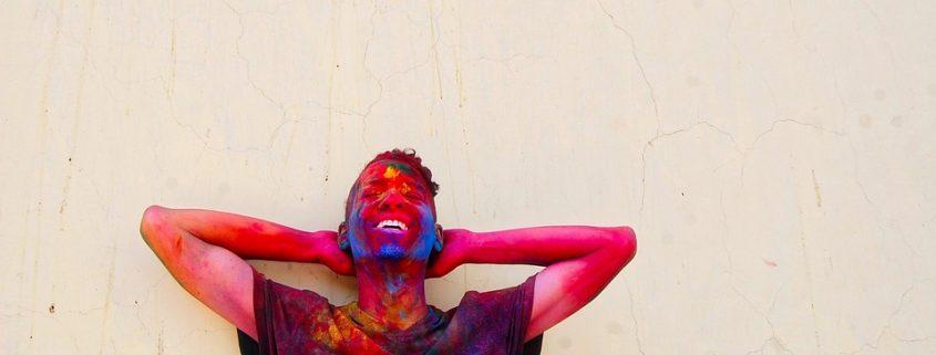 New Work Ästhetik Mann lachend mit buntem Gesicht nach Holi-Festival